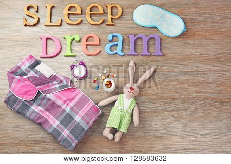 Words Dream and Sleep with little toy, pajamas also mask on a wooden background