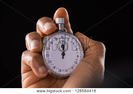 Close-up Of A Person Holding Stop Watch Over Black Background