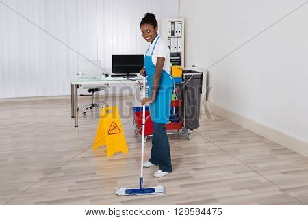 Female Janitor Mopping Wooden Floor With Caution Sign In Office
