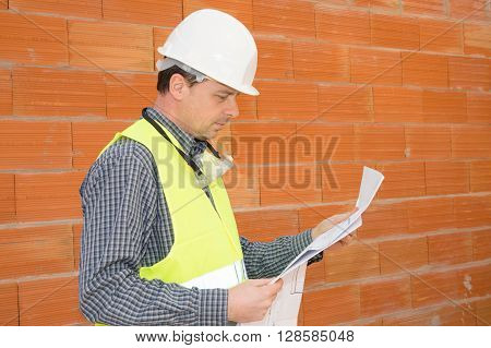 Construction Man On The Job Site Isolated Under Red Bricks