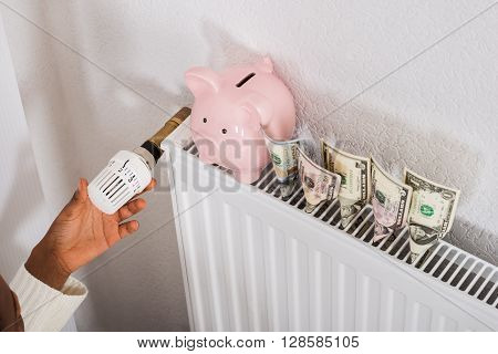 Close-up Of Woman Adjusting Thermostat With Piggy Bank And Bank Notes On Radiator