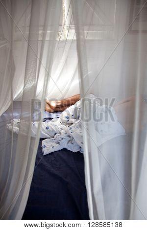Man sleeping behind mosquito net