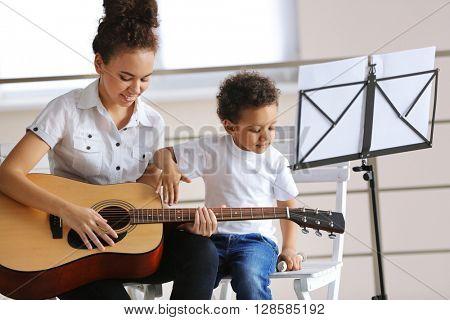 Young girl teaching little boy to play guitar
