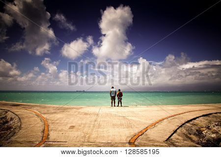 Father and son watching Caribbean sea from pier - Guadeloupe, Lesser Antilles - vintage photo