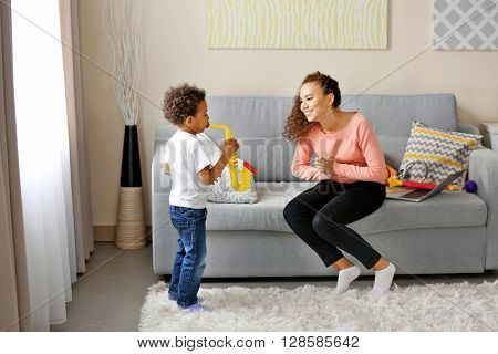 Young woman and little boy having fun in a living room