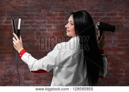 Beautiful woman with hair iron and hairdryer