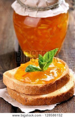 Orange jam on bread on wooden table