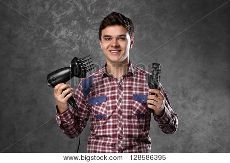 Handsome man with comb and hairdryer