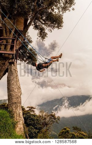 Silhouette Of Relaxing Teenager Man On A Swing Casa Del Arbol The Tree House Tungurahua Volcano Powerful Explosion On March 2016 In The Background Ecuador South America