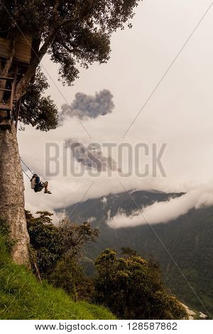 Young Boy Riding The Wildest Swing In The World Hanging From Casa Del Arbol The Tree House Above The Abyss Tungurahua Volcano Explosion On March 2016 In The Background Ecuador South America