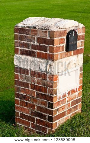 Red brick and white austin stone mailbox at a home with green grass in background.