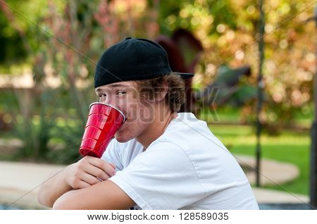 Teen boy outdoors with acne looking at camera with black backwards hat and white shirt.