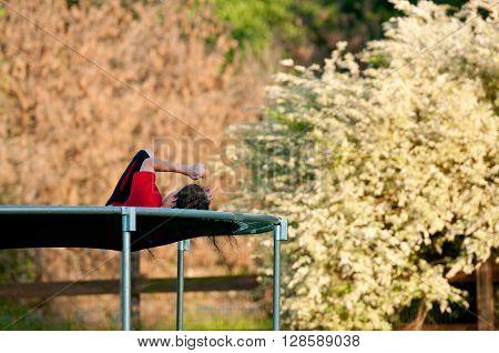 Teen boy on a trampoline outdoors in a backyard.