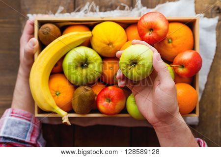 Man in tartan plaid shirt holds a box full of fresh fruits and a green apple. Fruit harvest - apples oranges lemon kiwi banana. Rustic wooden table.