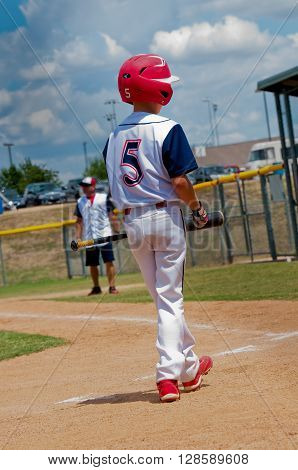 Young baseball player walking to home plate.