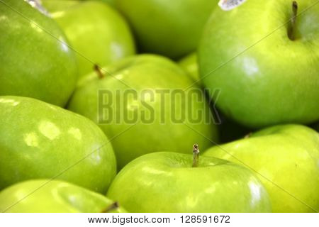 Close up of green apples stacked on top of eachother ** Note: Soft Focus at 100%, best at smaller sizes