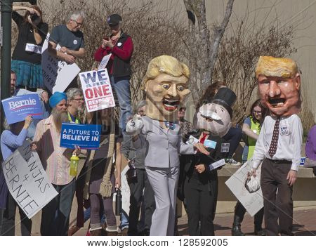 Asheville, North Carolina, USA - February 28, 2016: Effigies of Hillary Clinton and Donald Trump holding bags of money next to Mr. Monopoly as a crowd of Bernie Sanders supporters with signs confront them at a Bernie Sanders campaign rally