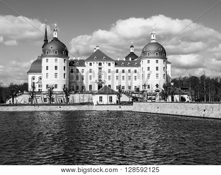Baroque castle of Moritzburg with yellow facade and red roof on sunny day, Saxony, Germany. Black and white image.