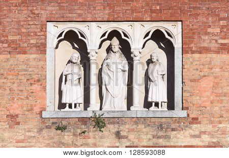 In the picture three statues located in the center the statue of Saint Ambrose Milan Italy.