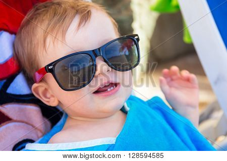 Cute baby boy in sunglasses on holidays at the pool