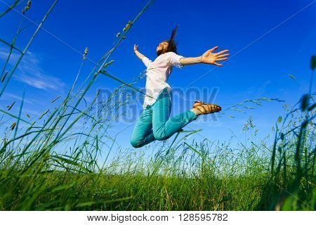 Young woman jump on green field