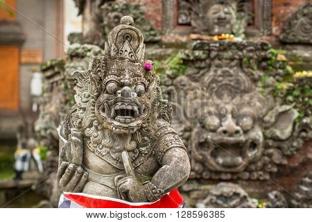 Traditional demon guard statue carved in stone on Bali island, Indonesia.