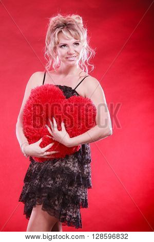 Woman mid aged blonde female wearing black evening dress holding big pillow in form of heart love symbol studio shot on red. Valentines day happiness concept