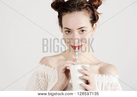 Lovely young girl is drinking with a straw with innocent smile on her face