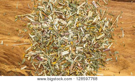 Heap pile of dried herb leaves on wooden surface. Herbaceous plant