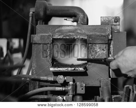 Locksmith turn on the furnace with a long lighter.