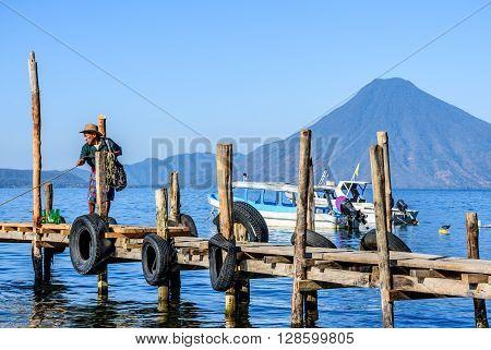 Lake Atitlan Guatemala - April 4 2016: Local man dressed in traditional Mayan pants pulls in boat from its mooring in early morning light with San Pedro volcano behind on Lake Atitlan, Guatemala.