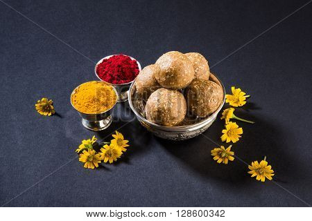 Huldi or turmeric and kumkum or kum kum with tilgul laddu or laddoo in silver bowl, sweet dish in Makar Sankranti festival in hindu religion in India, Indian sweet, isolated on black background