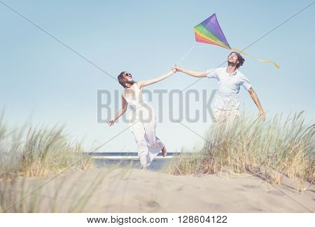 Cheerful Couple Playing Kite by the Beach