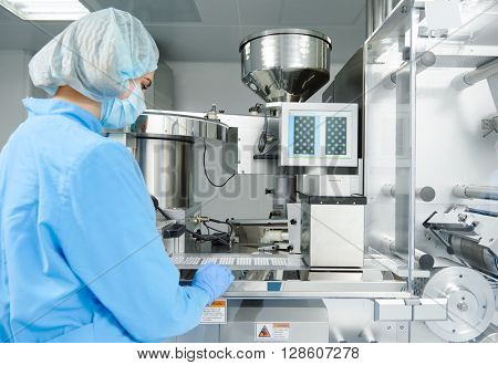 Pharmaceutics. Pharmaceutical worker operates blister packaging machine