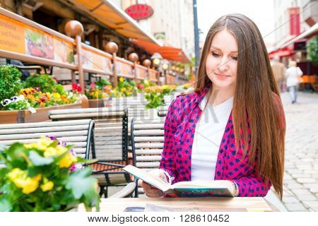 girl reading a book at an outdoor cafe