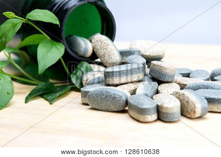 The Herbal Supplement vitamin pills or tablets on wooden plate