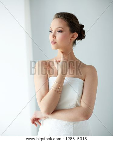 beauty, jewelry, wedding accessories, people and luxury concept - beautiful asian woman in white dress or bride with golden bracelet