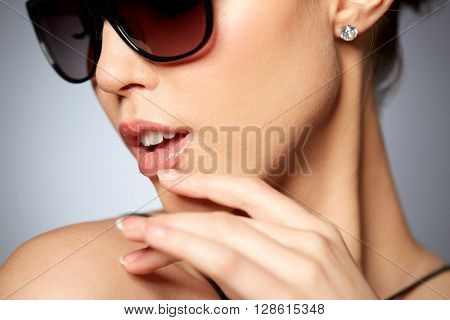 accessories, eyewear, fashion, people and luxury concept - close up of beautiful young woman in elegant black sunglasses over gray background