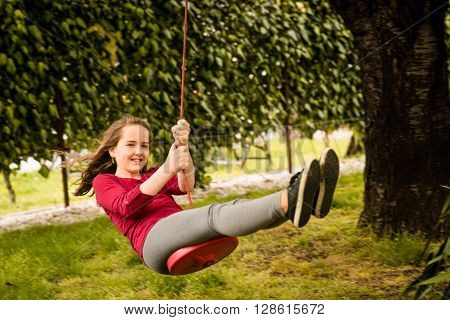 Happy girl swinging on seesaw hanging from cherry tree behind family house