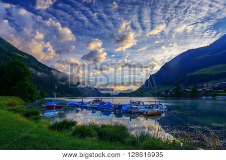 Amazing view of the Lungerersee lake with yachts in the morning mist. Lungern village, Switzerland, Europe.