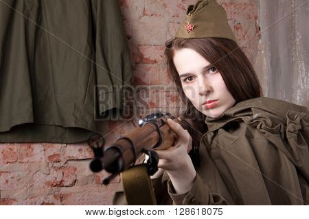 Woman in Russian military uniform shoots a rifle. Female soldier during the second world war.