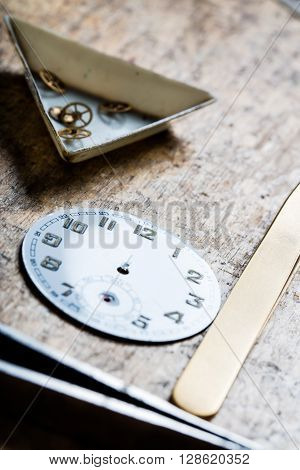 Antique Watch Quadrant And Clockworks On A Repair Table