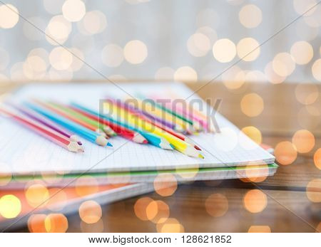 school, education, drawing and object concept - close up of crayons or color pencils on notebook paper over holidays lights background