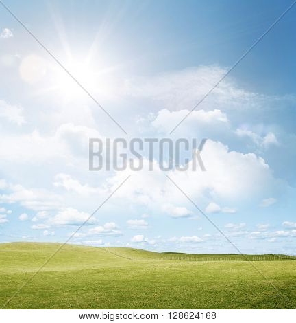 Green grass and sun in blue sky