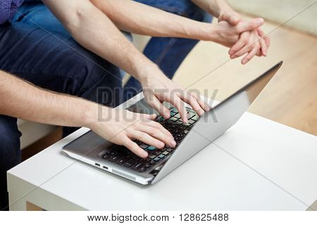 friendship, technology and people concept - close up of male friends with laptop computer at home