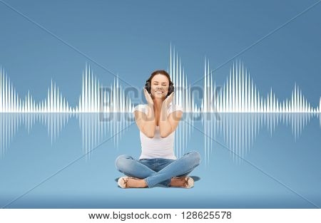 technology, music and happiness concept - smiling young woman or teen girl in headphones over blue background and sound wave or diagram