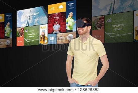 3d technology, virtual reality, mass media, entertainment and people concept - happy young man in virtual reality headset or 3d glasses with screens projection over black background