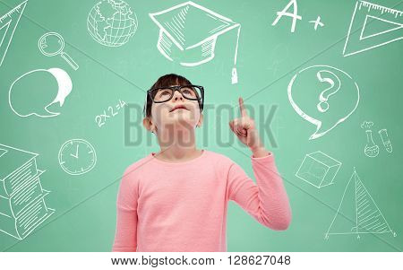 childhood, school, education, vision and people concept - happy little girl in eyeglasses pointing finger up over doodles on green chalk board background