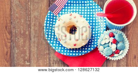 american independence day, celebration, patriotism and holidays concept - close up of glazed sweet donut with juice and candies in disposable tableware on wooden table at 4th july party from top
