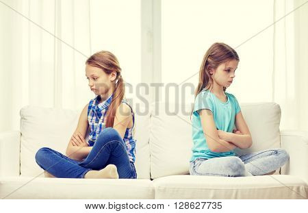 people, children, friends and friendship concept - quarreled angry little girls sitting on sofa back to back at home